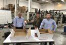 Uwe Streiber, Lead Verpackungsmanagement (Mitte) und Alex Astanin, Junior Manager Verpackungsmanagement (rechts), beide bei Zalando SE, sind vom Re-Design der Verpackung begeistert. Dank des Automatikbodens spart die optimierte Lösung (rechts im Bild) gegenüber der alten Krempelverpackung (links im Bild) wertvolle Sekunden beim Aufrichten. Entwickelt wurde die Lösung von dem Display- und Verpackungsstrategen DS Smith (hier vertreten durch Key Account Manager Rainer Büttner, links).